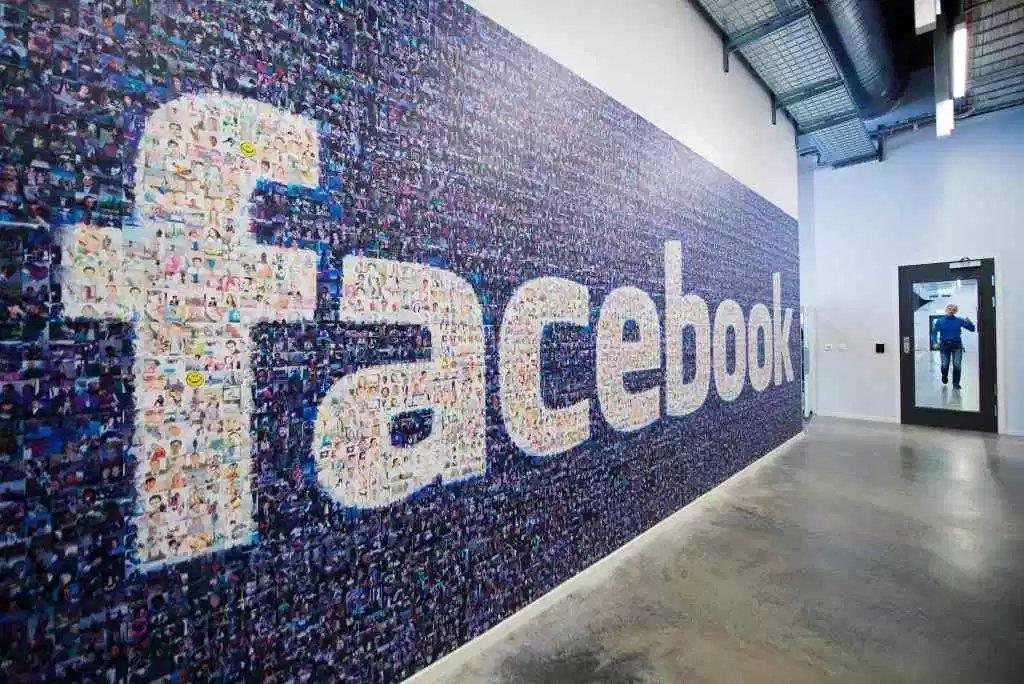 Facebook logo em parede de fotos