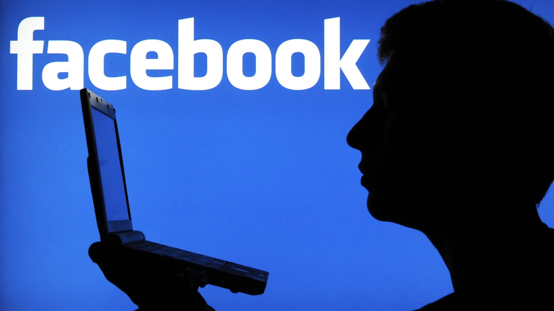 Facebook em computador com pessoa à frente