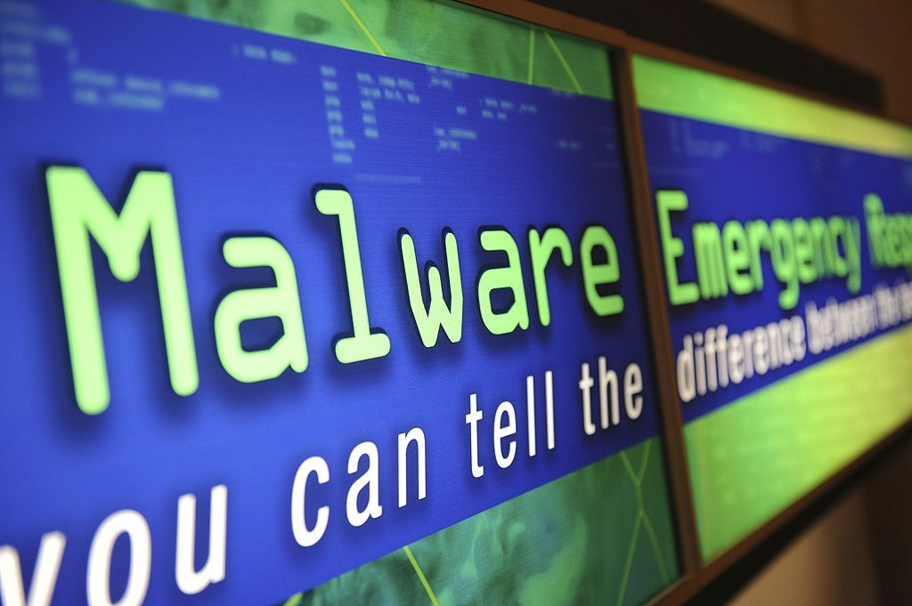 Computadores com malware escrito em letras grandes