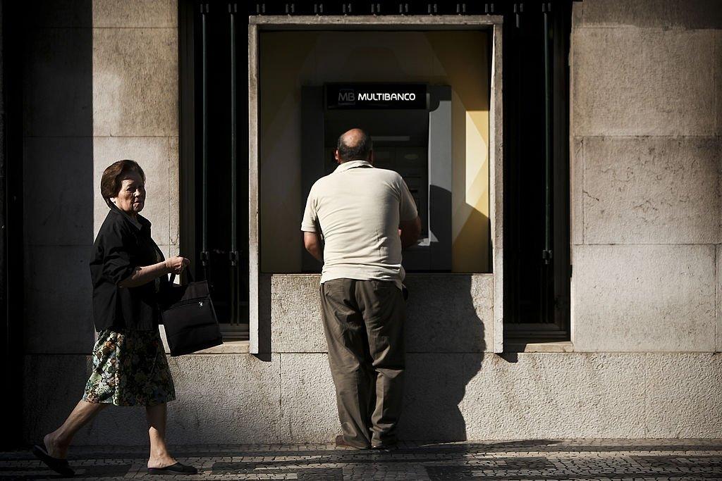 Caixa de multibanco com homem a pagar