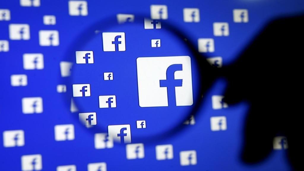 Facebook logo sobre uma lupa