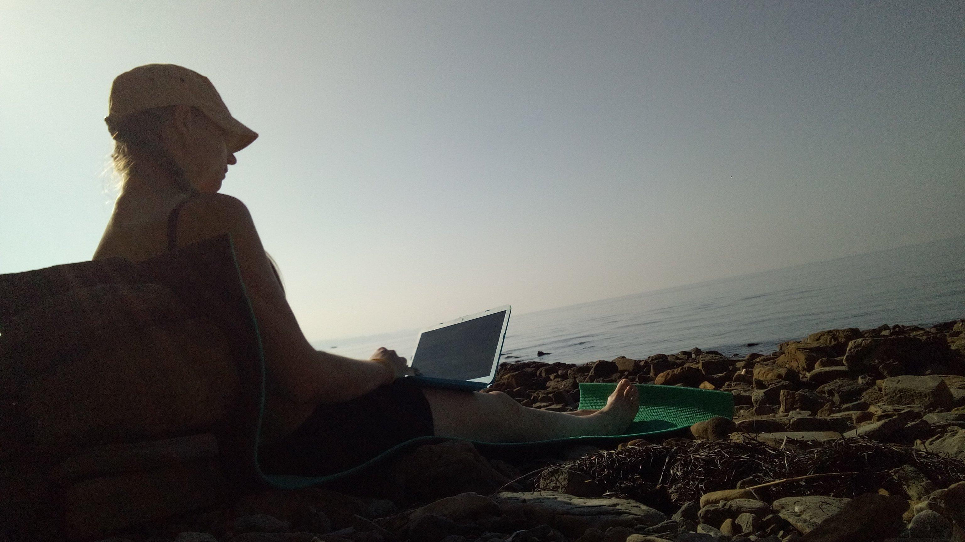 Praia rapariga com computador no colo