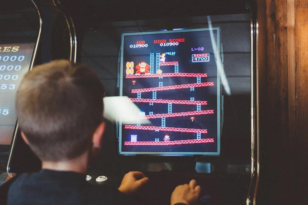 Criança a jogar arcade