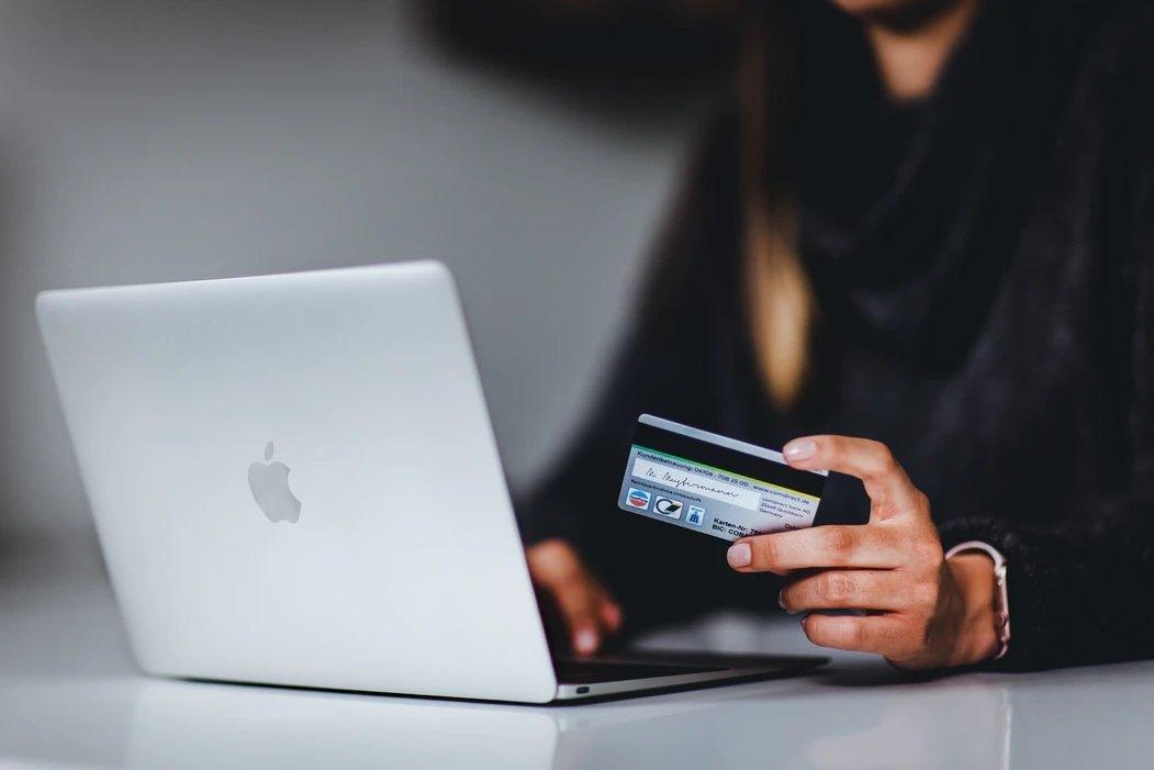 Pessoa a comprar pelo computador com o cartão de crédito
